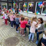 Dzieci karmiące Panie siedzące na krzesłach przed przedszkolem. Po lewej stronie, na krzesłach siedzą dzieci. Budynek przedszkola udekorowany jest balonami i wiatrakami.