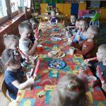 Grupa dzieci jedząca lody, siedząca przy wspólnym stole w sali przedszkolnej.