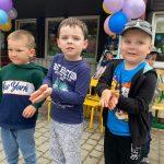Trzech chłopców stojących przed przedszkolem. W tle widać dziecko siedzące w wózku, który trzyma Pani.