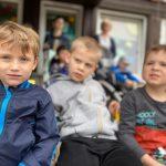 Trzech chłopców siedzących na krzesłach przed budynkiem przedszkola. W tle widoczne są dwie Panie trzymające wózkii, w których siedzą dzieci.