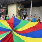 Trzynaścioro dzieci znajdujących się przedz przedszkolem i trzymających w rękach kolorową chustę. Budynek przedszkola jest udekorowany balonami.