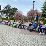 Dzieci siedzace w ogrodzie przedszkolnym na krzesłach w jednym rzędzie. Za dziećmi stoi Pani.