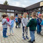Grupa dzieci tańczacych na placu przedszkola w parach. W tle widoczne są dwie Panie i dzieci siedzące na krzesłach.