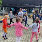 Dwie Panie tańczące w kółku z dziećmi na placu przedszkola. W tle widoczna jest Pani trzymająca na rękach chłopca. Po prawej stronie widać dwie Panie z dziećmi. Budynek przedszkola jest udekorowany balonami.