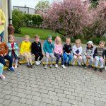Grupa dzieci siedzących na krzesłach na placu przedszkola. Za dziećmi widać dwie Panie.
