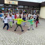 Grupa dzieci tańczących w kołach na placu przedszkolnym. W tle, po prawej stronie widoczne są dwie Panie nauczycielki. Budynek przedszkola udekorowany jest balonami oraz wiatrakami.