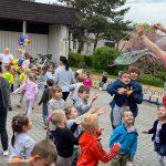 Pani puszczająca bańki mydlane na placu przedszkolnym. Przed Panią stoją dzieci. Jedna Pani trzyma na rękach chłpca. W tle widocznych jest pięć Pań.
