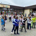 Grupa dzieci tańczących w parach na placu przedszkolnym.
