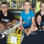 3 chłopców siedzi na dywanie. Przed nimi leży pszczoła wykonana z butelki plastikowej.