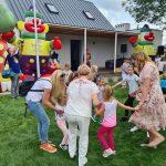 Dzieci i Panie na dworze trzymają się za ręce tworząc koło