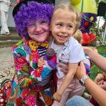Uśmiechnięta dziewczynka z klaunem.