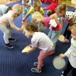 Dzieci stoją na dywanie trzymając ręce na dole.