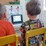 2 chłopców siedzi na krześle. Oglądają bajke na laptopie