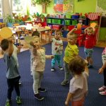 Dzieci stoją na dywanie trzymając ręce do góry .