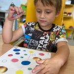 Chłopiec siedzi przy stoliku.Łączy pisakiem na kartce kolorowe kropki.