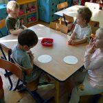Dzieci siedzą przy stoliku i koloroują papierowe kropki.