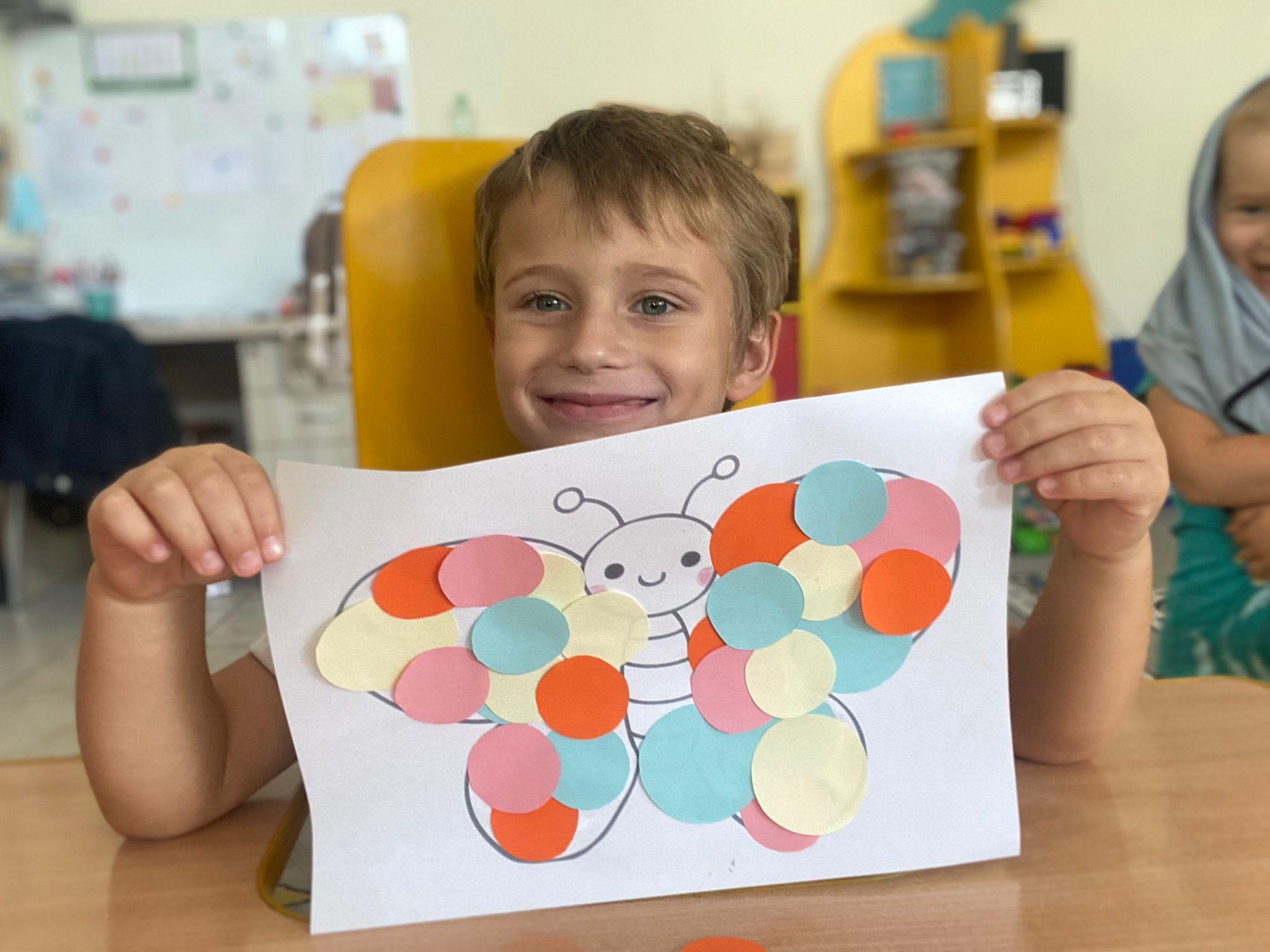 Chłopiec siedzi przy stolik. Trzyma w rękach Wyklejonego motyla kółkami.