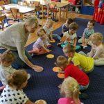 Dzieci z Panią siedzą na dywanie. Przed sobą trzymają papierowe kropki.