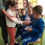 Dziewczynka trzymana za ęce przez Panią, podaje chłopczykowi zapakowany upominek ( chłopiec siedzi na krześle)