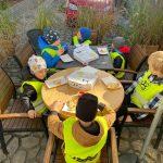 6 chłopców siedzących na krzesłach przy stole. na środku leżą kartony od pizzy.
