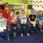 5 chłopców siedzi na krześle. w rękach trzymają zapakowaną w celofan książkę