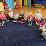 Grupa dziewczynek siedzących na dywanie.