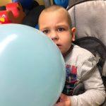 Chłopiec siedzi na wózku trzymając w rękach balon.