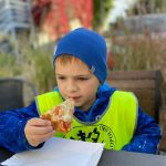 Chłopiec jedzący kawałek pizzy.