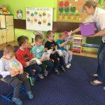 5 chłopców siedzi na krześle. w rękach trzymają zapakowaną w celofan książkę. Pani trzymając w ręce koszyk podaje prezent ostatniemu chłopczykowi.