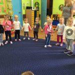 grupa dziewczynek stojących na dywanie , trzymając się za ręce.