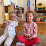 Dwie dziewczynki siedzące na dywanie w sali przedszkolnej.