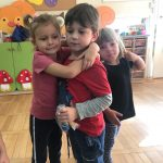 Dziewczynka przytulająca chłopca, który trzyma w ręku upominek. Z tyłu stoi dziewczynka.