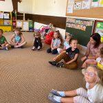 Grupa dzieci siedzących na dywanie w półkolu. Po prawej stronie między dziećmi siedzi nauczycielka.