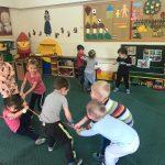 Dwie grupki dzieci przeciągających linę w sali przedszkolnej.