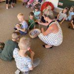 Grupa dzieci siedzących na dywanie w sali przedszkolnej. Przed dziećmi Pani nauczycielka częstuje dzieci lizakami, znajdującymi się w koszyczku.