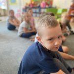 Chłopiec siedzący na dywanie w sali przedszkolnej. W tle widoczna grupa dzieci.