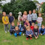 Grupa dzieci pozująca do zdjęcia w ogrodzie przedszkolnym. Pomiędzy dziećmi, w drugim rzędzie stoi alpaka, którą trzyma dziewczynka.