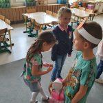 Na pierwszym tle troje dzieci stojących w sali przedszkolnej. Chłopiec częstuje dziewczynki lizakami. W tle stoją trzy dziewczynki.