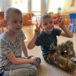 Dwóch chłopców siedzących na dywanie w sali przedszkolnej.