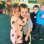 Czworo dzieci stojących w sali przedszkolnej. Na pierwszym planie dziewczynka przytula chłopca, z tyłu przytula się dwóch chłopców.