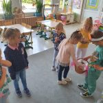Dzieci stojące w sali przedszkolnej w rozsypce. Chłopic trzyma w ręku koszyk i częstuje dziewczynkę lizakiem.