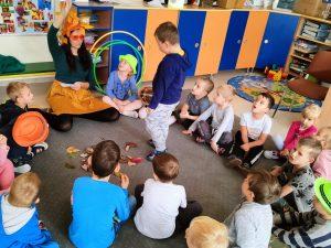 Grupa dzieci siedzących w sali w kole na dywanie. Pomiędzy dziećmi msiedzi Pani przebrana za Pania Jeszień. W środku koła stoi chłopiec.