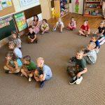 Grupa dzieci siedzących wraz z Panią na dywanie w sali przedszkolnej.