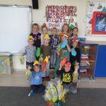 Grupa dzieci stojących pod tablicą w sali przedszkolnej. Chłopcy mają na głowach opaski i trzymają w rękach papierowe krawaty.