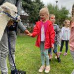 Dziewczynka karmiąca marchewką alpakę, którą trzyma chłopak. za dziewczynką stoi chłopiec i dziewczynka.