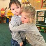 Dwoje przytulających się dzieci w sali przedszkolnej.