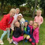 Ośmioro dzieci będących w ogrodzie przedzskolnym, pomiędzy którymi siedzi alpaka.