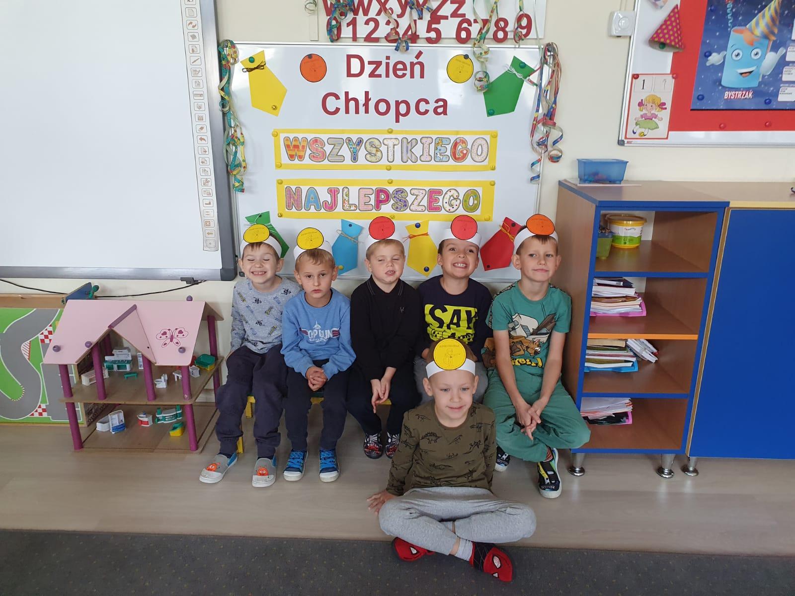 Pięcioro chłopców siedzących na ławce w sali przedszkolnej. Przed dziećmi siedzi chłopiec po turecku. Wszyscy chłopcy mają na głowach opaski.