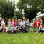 Grupa dzieci wraz z dwiema Paniami i dwiema alpakami pozujący do zdjęcia w ogrodzie przedszkolnym.