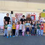 Grupa dzieci pozujących do zdjęcia w sali przedszkolnej. Za dziećmi stoi pięć Pań.